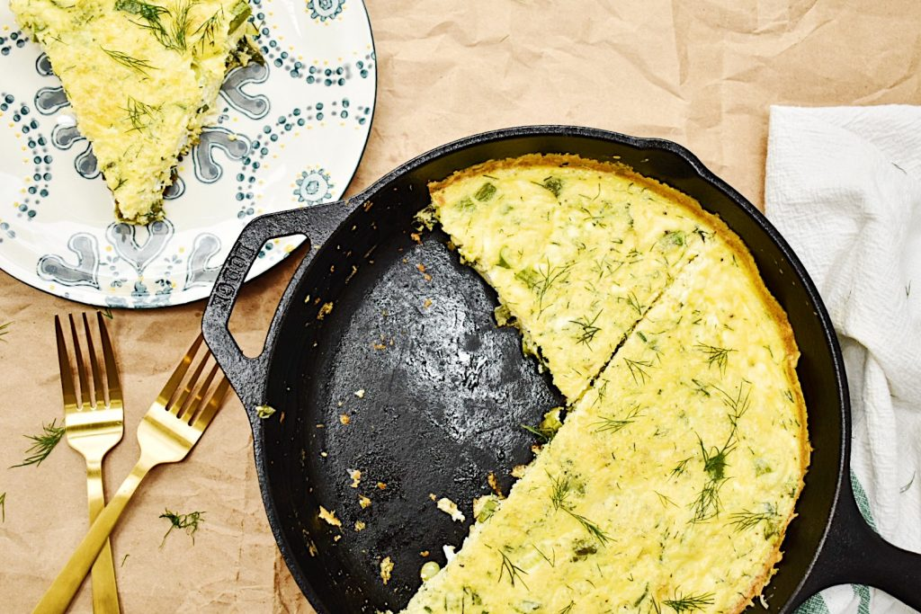 asparagus and spring onion frittata in black pan with slice taken out on plate