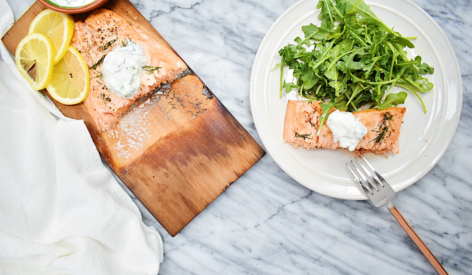grilled salmon with yogurt sauce on cedar plank with one slice cut out and on white plate with arugula salad