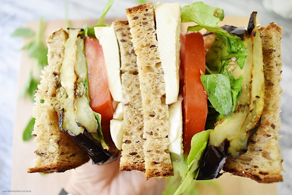 two halfs of a grilled eggplant caprese sandwich in one hand