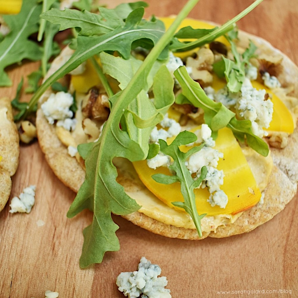 45 degree angle of grilled hummus pizza with gorgonzola, beets and arugula on wood background