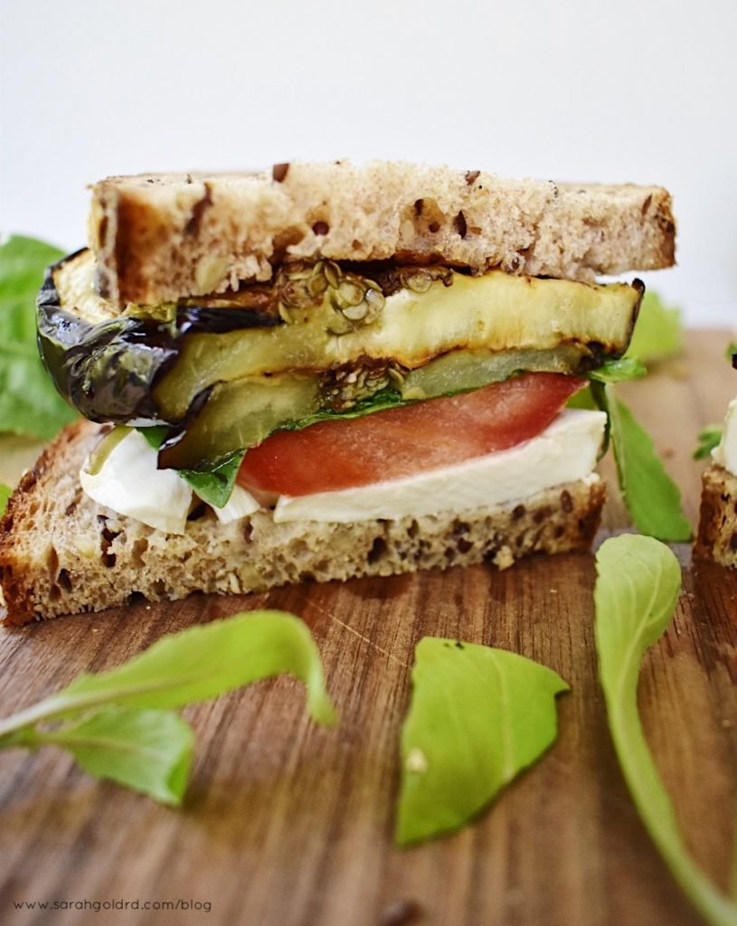 half of a grilled eggplant caprese sandwich with arugula on a wood cutting board