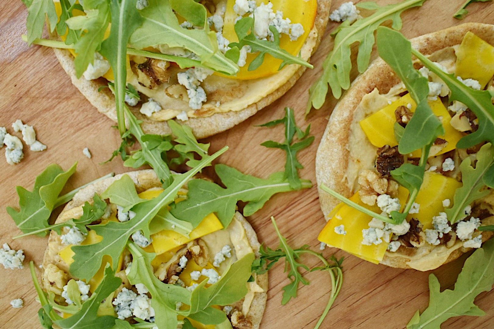 grilled pita pizzas on wood background
