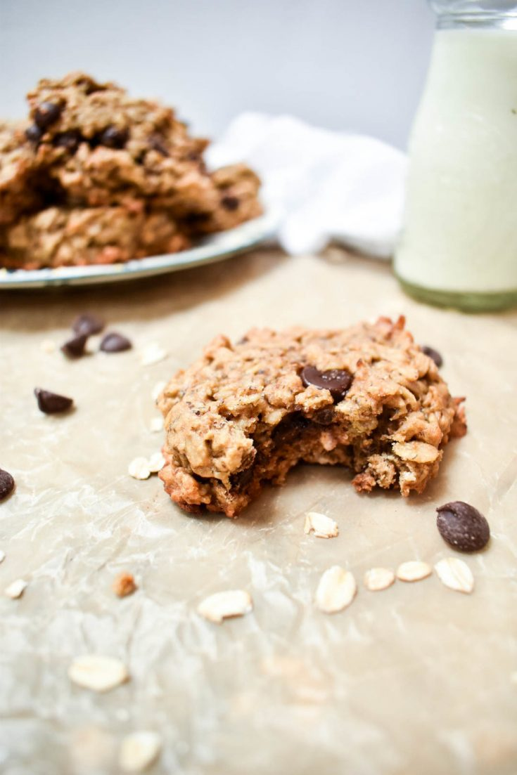 peanut butter breakfast cookie with bite in front of a plate with a pile of cookies and a small jar of milk on wax wax paper background
