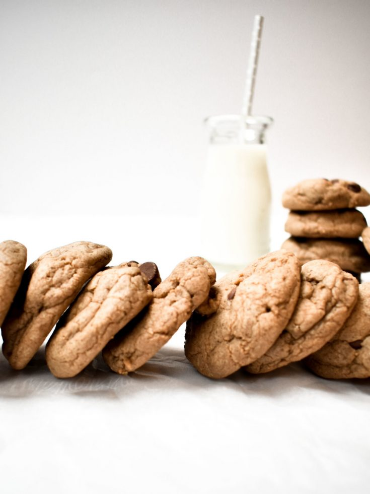row of chocolate chip cookies with glass of milk