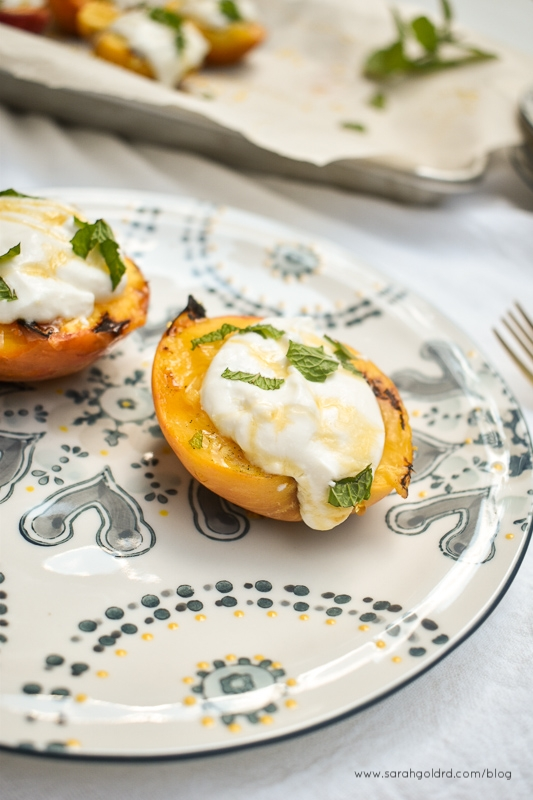 close up of two grilled peaches with honey ricotta and fresh mint on blue and white plate