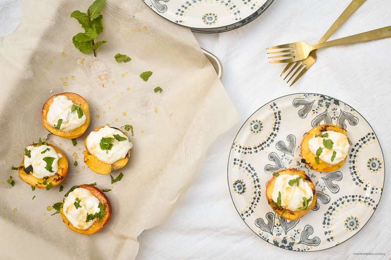 grilled peaches with honey ricotta on sheet pan with two on blue flowered plate