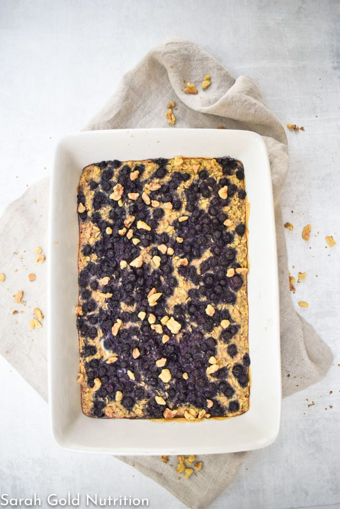 high protein baked oatmeal with blueberries in white dish and tan twel