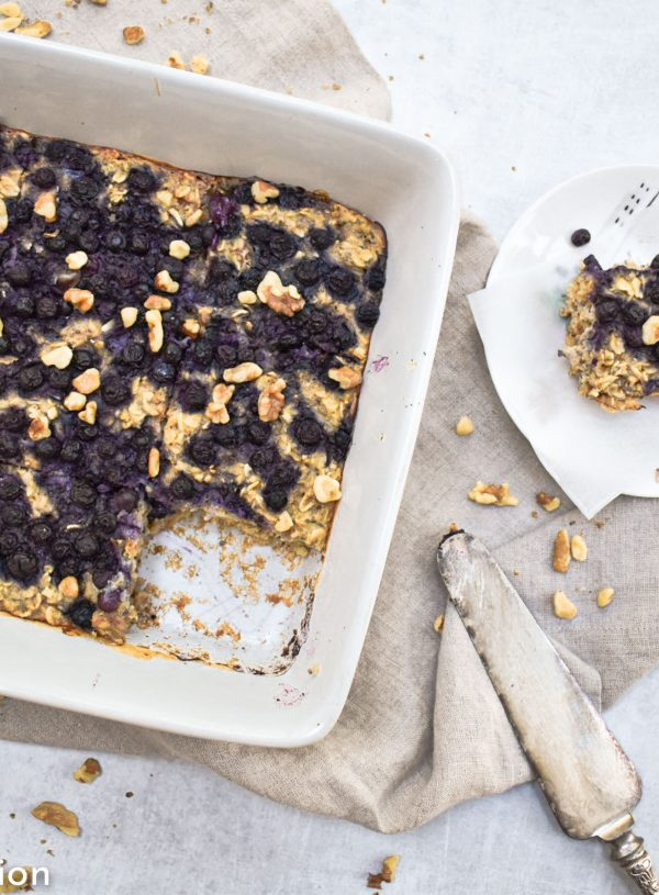 blueberry high protein baked oatmeal in white dish with tan background and small slice cut out on white plate.