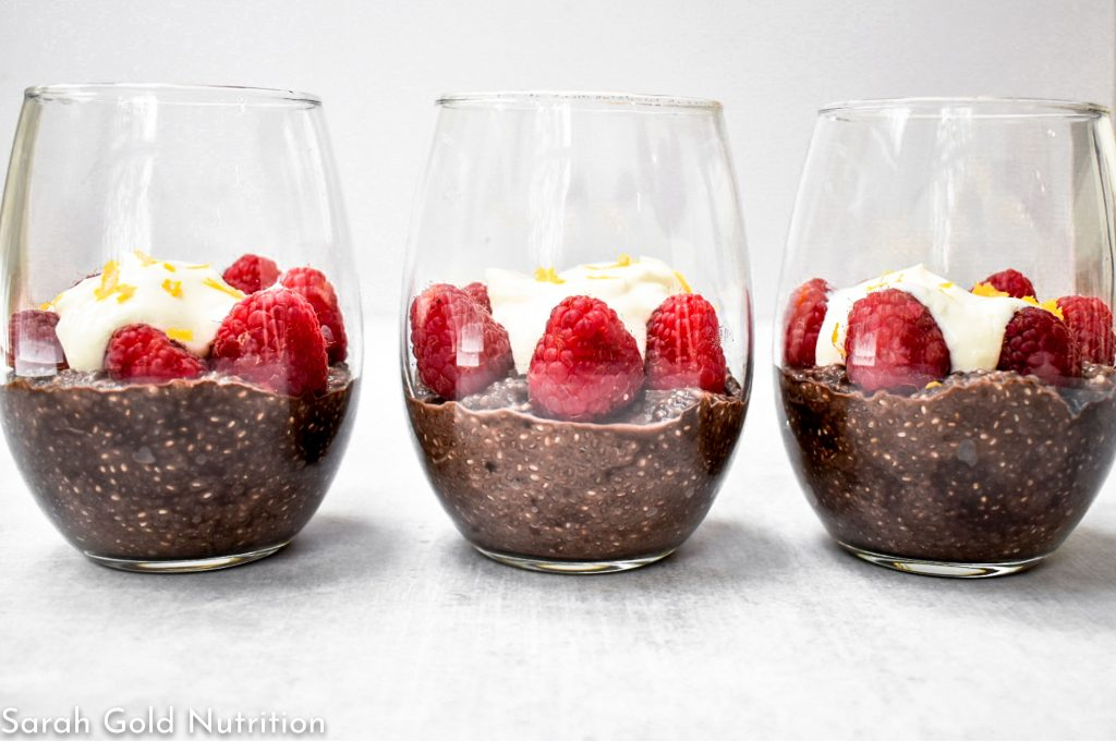 dark chocolate chia pudding with raspberries and cream in stemless wine glasses on gray background