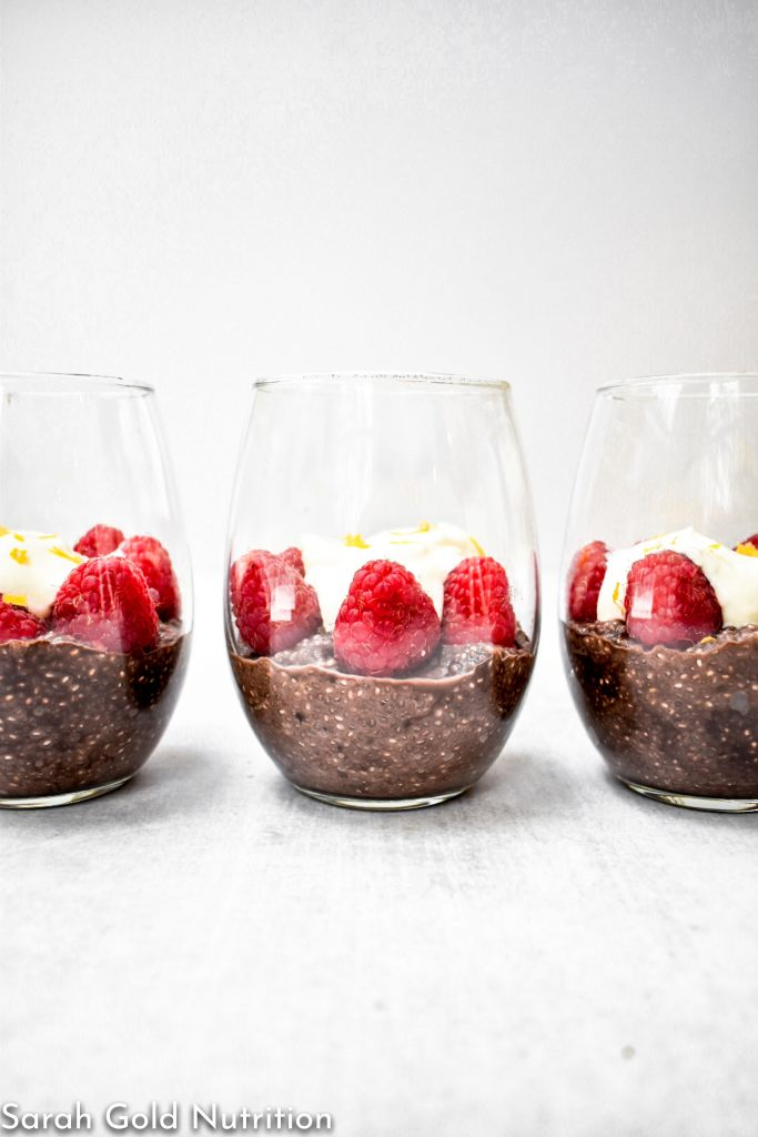 3 wine glasses filled with dark chocolate chia pudding topped with raspberries and yogurt with meyer lemon zest on grey background.