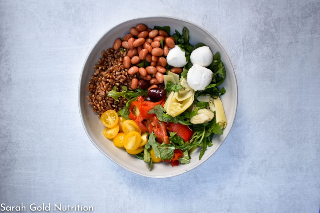 overhead shot of wheat berry caprese grain bowl on grey background. white bowl filled with wehat berries, beans, fresh mozzarella, tomatoes, roasted red peppers, argugula, and artichoke hearts.
