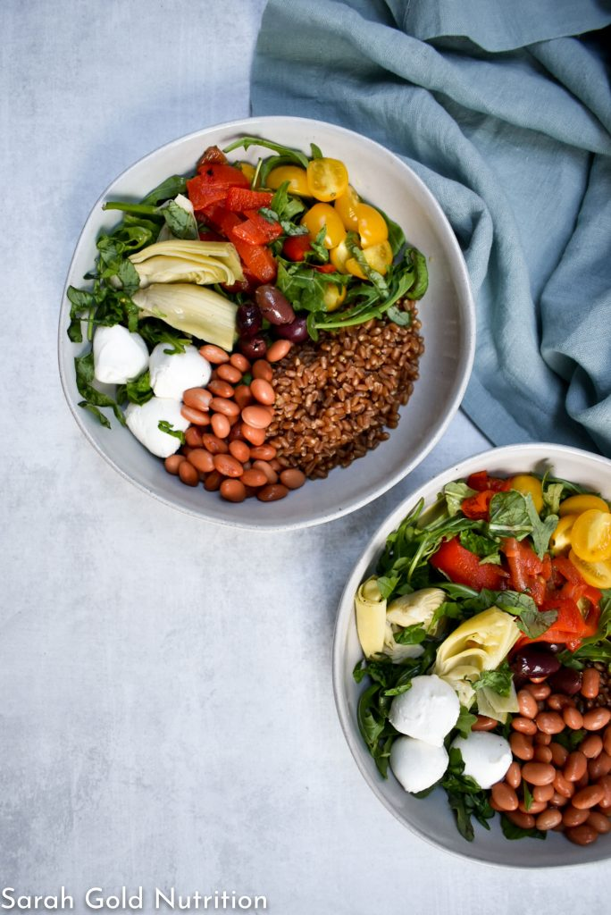 grey background with light blue cloth napkin. 2 bowls filled with wheat berry caprese grain bowl, which includes beans, arugula, artichoke hearts, tomatoes, roasted peppers, and basil.