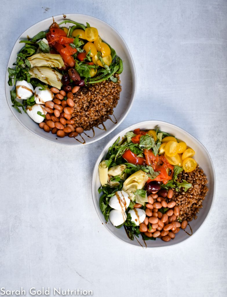 overhead shot of wheatberry caprese grain bowl on grey background