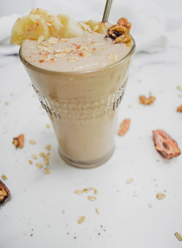 chickpea smoothie on white marble background with oats and dates scattered. image at 45 degree angle