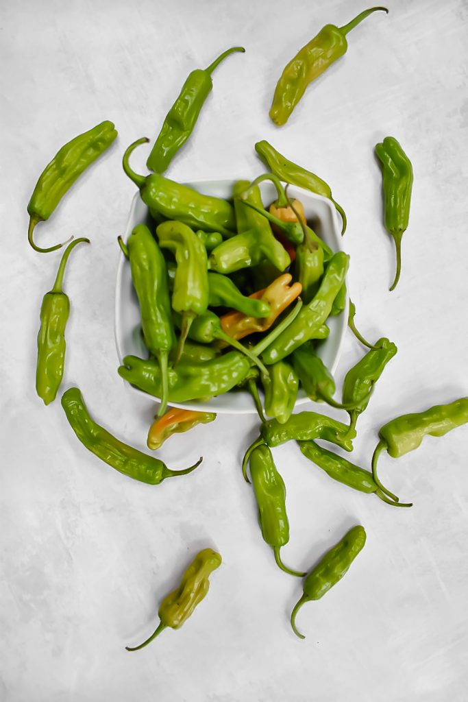 shishito peppers in white basket on grey background