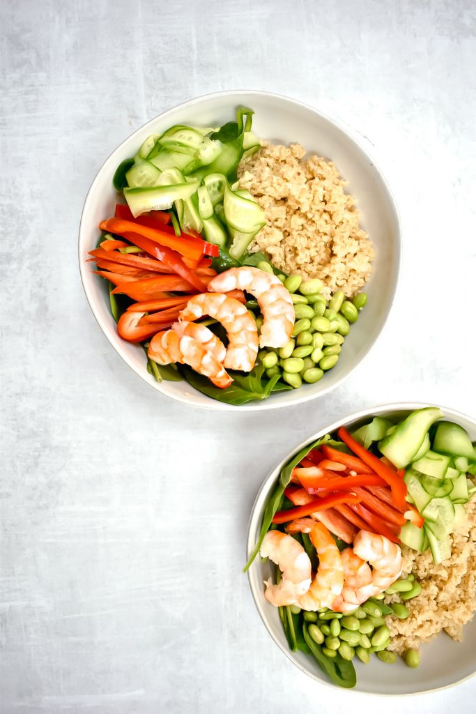 two shrimp and quinoa power bowls on grey background