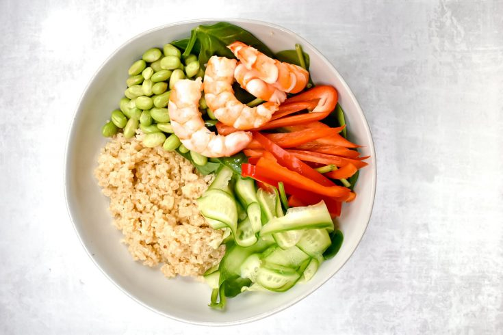 white bowl with shrimp quinoa, edamame, red pepper, cucumber on grey background