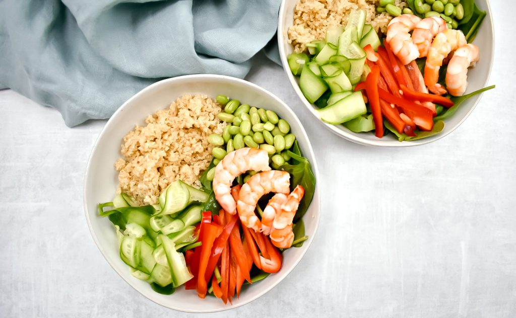 two shrimp and quinoa power bowls with edamame, cucumber, red pepper, and spinach on grey background with blue linen