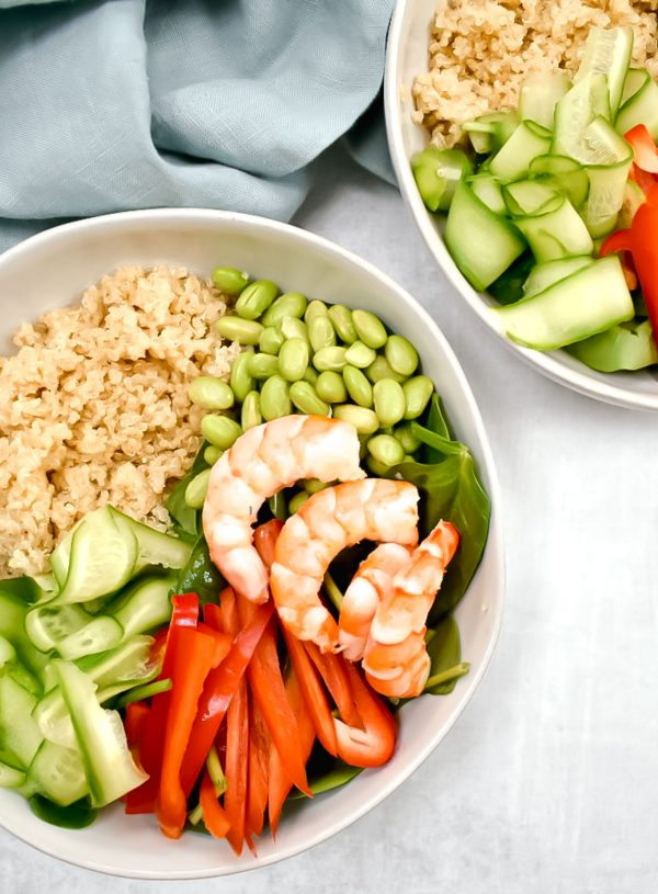 quinoa power bowl with shrim, edamame, cucumber, and red pepper on grey background with blue linen