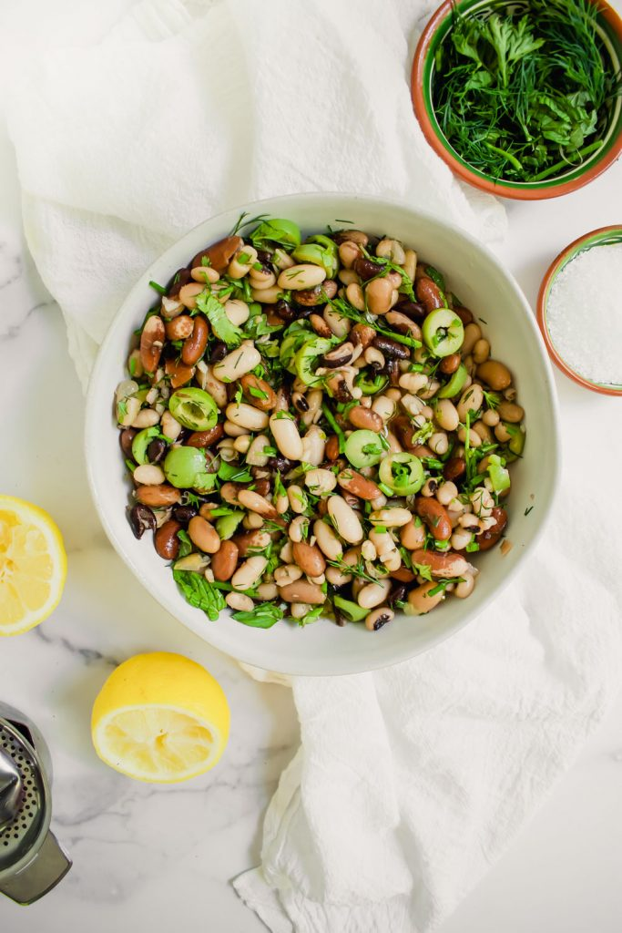 overhead shot of easy bean salad with olives and herbs in large white bowl with lemons and bowl of herbs and salt on marble background