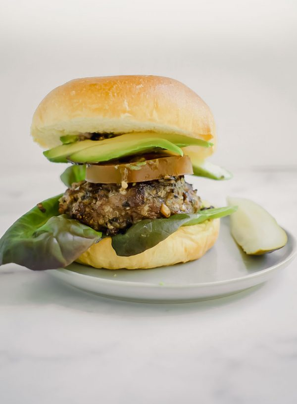quinoa and mushroom blended burger on plate with pickle