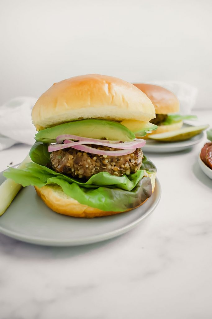 blended burger on a bun with avocado and onion on a grey plate