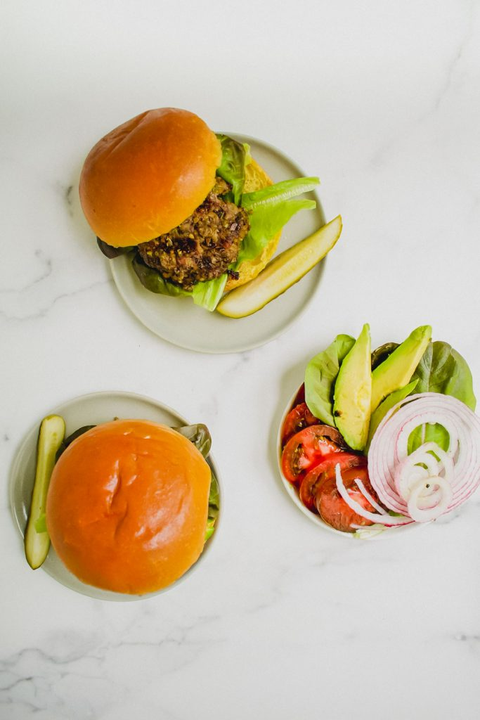 overhead shot of quinoa mushroom blended burger with plate of lettuce, onion, tomato, and avocado