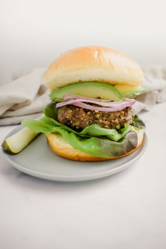 quinoa mushroom blended burger on bun topped with avocado and onion on grey plate with pickel