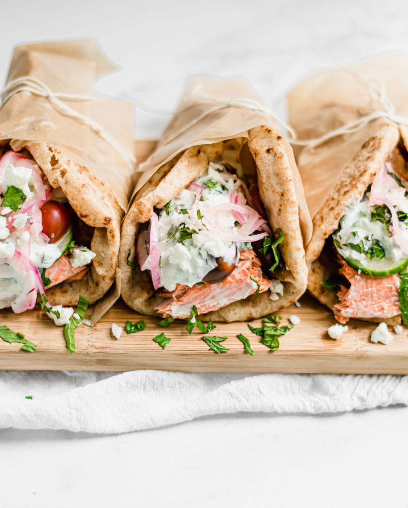 straight on shot of salmon gyros on cutting board with white towel