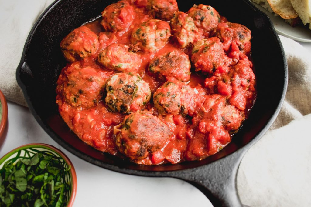 meatballs in cast iron pan with chopped mint in bowl on the side.