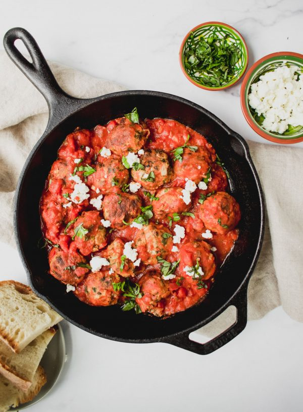 overhead shot of greek turkey meatballs with feta cheese in cast iron pan