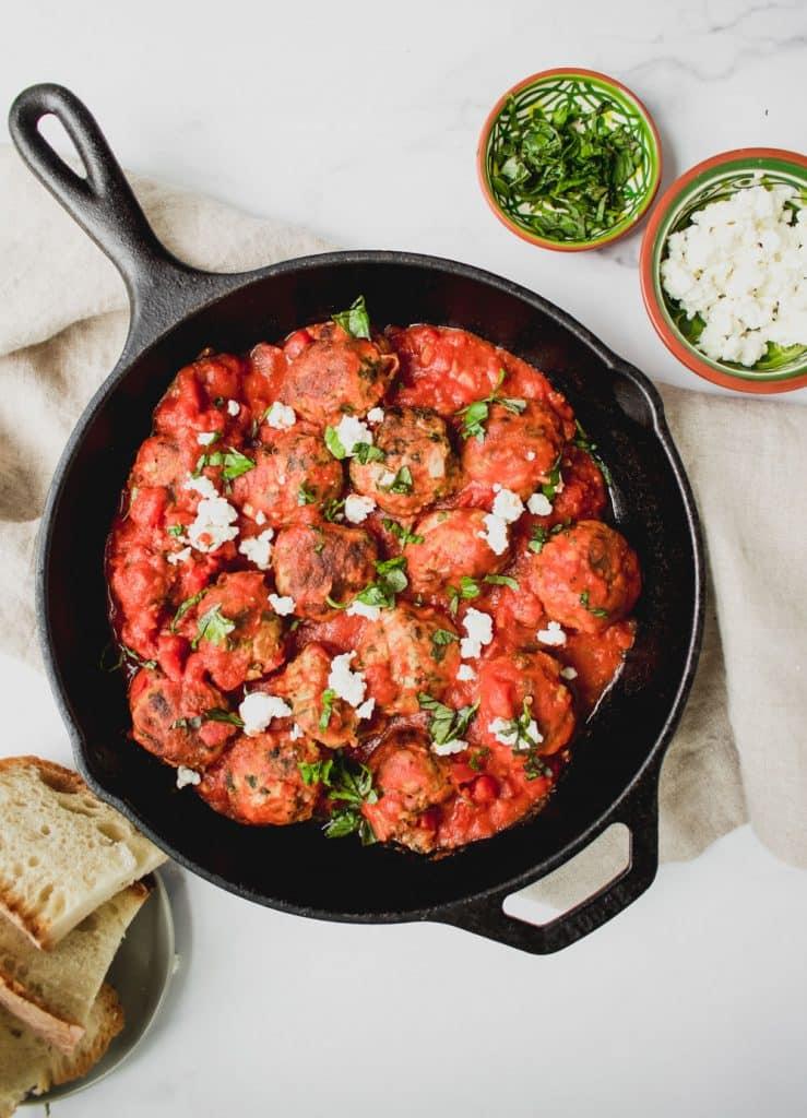 overhead shot of greek turkey meatballs with feta cheese in cast iron pan