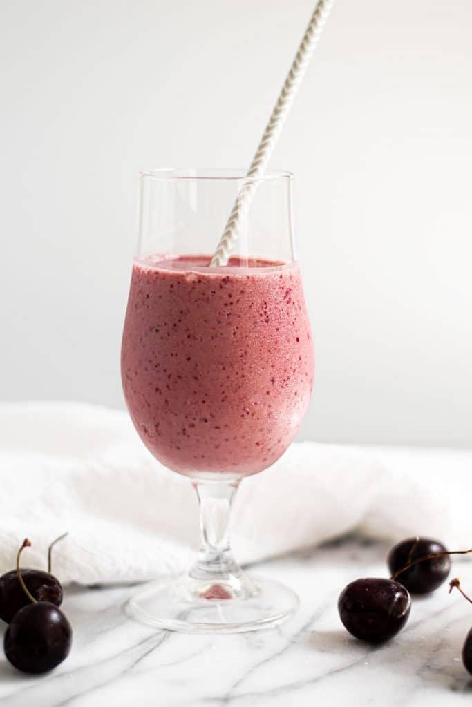 cherry vanilla smoothie in milkshake glass with straw on marble background