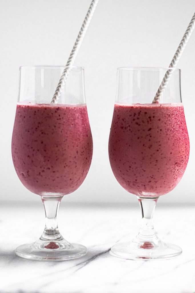 2 cherry vanilla smoothies with straws in fancy glass