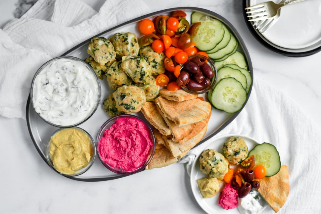 platter with greek meatballs, pita, dips ,and veggies plus small plate filled with platter ingredients next to it.=