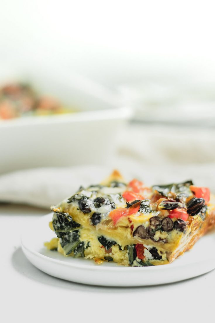 slice of casserole on small white plate with baking dish in background