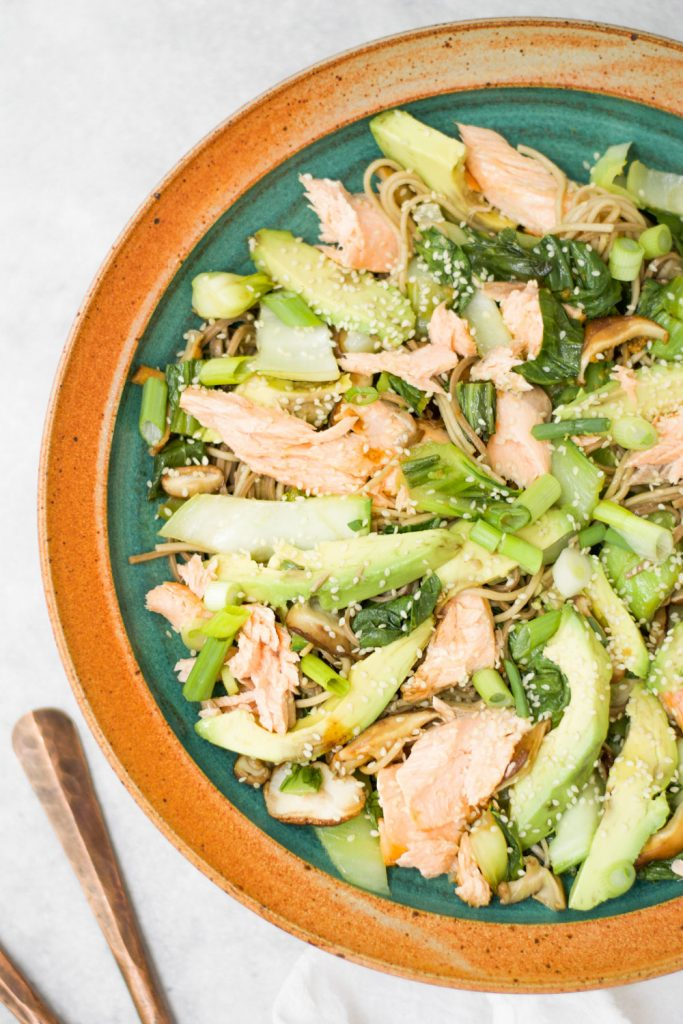 overhead image of salmon soba noodle salad with spoons on the side of the dish on gray background